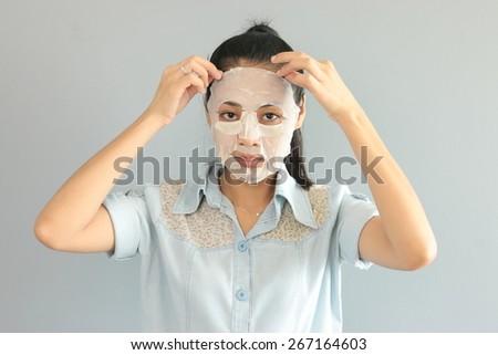 Thai woman put on facial mask. - stock photo