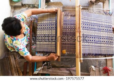 Thai woman weaving traditional straw mat using Cyperus alternifolius stems, Khon Kaen, Thailand - stock photo