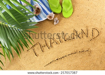 Thailand beach writing with towel, palm leaves and sandals - stock photo