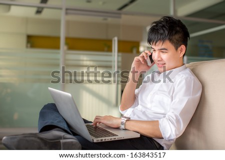 Thailand business man talking on a mobile phone and working on his laptop - stock photo