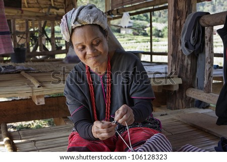 Thailand, Chiang Mai, Karen Long Neck hill tribe village (Kayan Lahwi), a Karen woman in traditional costumes is making a carpet - stock photo