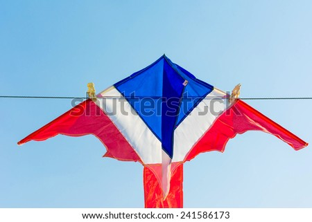 Thailand flag color kite hanging on string against cloudless blue sky - stock photo