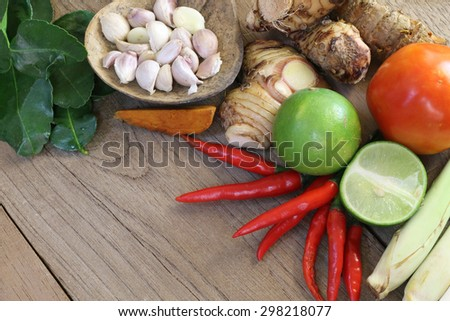 Thailand Food Ingredients: lemon, lime, galangal, ginger, tomato, mango leaves the dungeon, garlic on a wooden floor. - stock photo