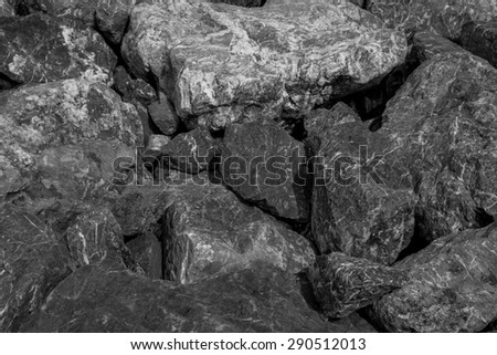 Thailand / June 2015. Black and White Rocks background. The rocks was scattered along the shore line to prevent land erosion and it creates nice pattern. - stock photo