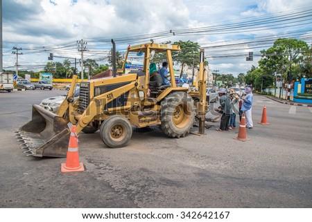 Thailand 2015 Nov 23, excavator and worker on site for road mantanance in Chantaburi junction,Chantaburi town,Thailand. - stock photo