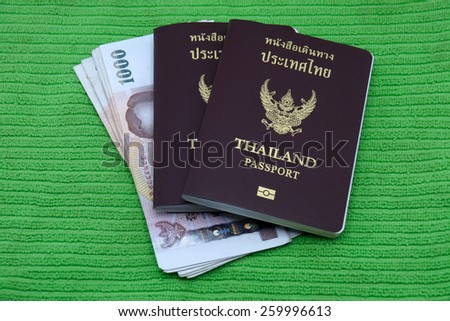 Thailand passport and Thai money isolated on green background - stock photo