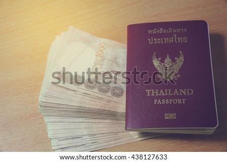 Thailand passport and Thai money savings - stock photo