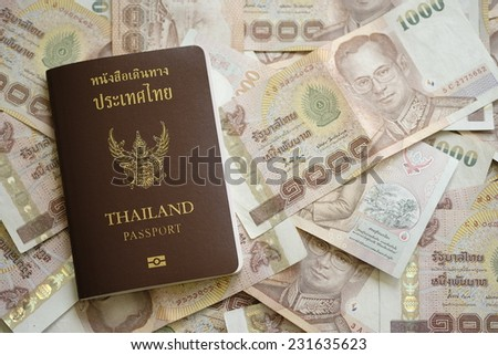 Thailand passport with Thai money ready to trave - stock photo