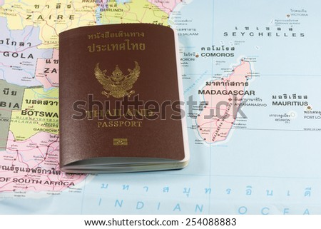 Thailand Passports on a map of the Madagascar. - stock photo