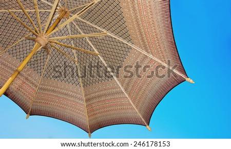 Thailand pattern silk umbrella and sky blue art artist handicraft beach. - stock photo