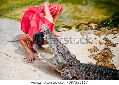 """Thailand, Samut Prakan - Otober, 25, 2009 : Unidentified zoo keeper puts a head in a mouth of the crocodile as part of """"Show of crocodiles"""" at Samut Prakan Crocodile Farm and Zoo. - stock photo"""