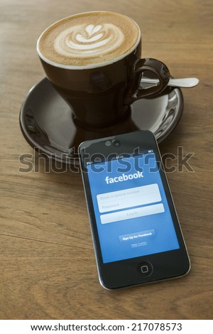 THAILAND - SEPTEMBER 05, 2014: Facebook application login screen on ipod apple product with morning coffee and wood desk background. - stock photo