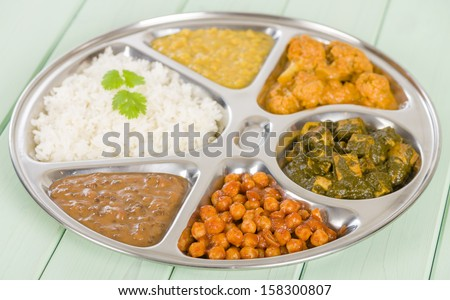 Thali - South Asian selection of vegetarian curries and rice served in a traditional dish. Taka dahl, gobi masala, palak paneer, chana masala and dahl makhani. - stock photo