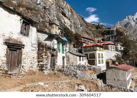 Thame gompa with prayer flags and buddhist symbols - monastery in Khumbu valley on three passes trek, Mount Everest area, Sagarmatha national park, Nepalese Himalayas - stock photo
