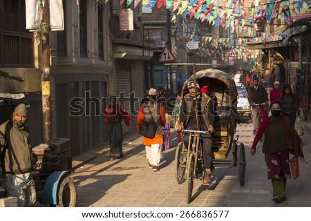 THAMEL, KATHMANDU, NEPAL - NOVEMBER 20, 2014: Rickshaws driving by the street of Kathmandu, Nepal on November 20. Rickshaws are the means of transport with the lowest cost in Kathmandu. - stock photo