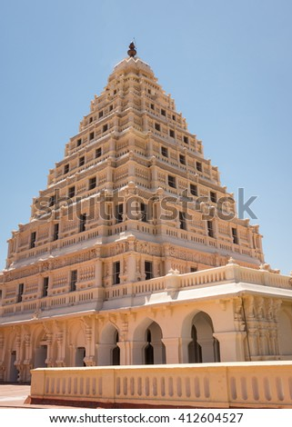 Thanjavur, India - October 14, 2013: The beige Arsenal Tower at Thanjavur Palace against a blue sky. Corner shot shows front and side. Lakshmi and other decorations worked in frescos. - stock photo