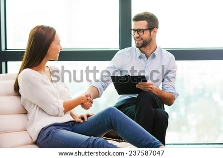 Thank you doctor! Cheerful male psychiatrist shaking hand to beautiful young woman sitting close to him  - stock photo