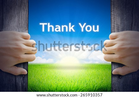 Thank You. Hands opening a wooden door then found a texts floating among new world as green grass field, Blue sky and the Sunrise. - stock photo
