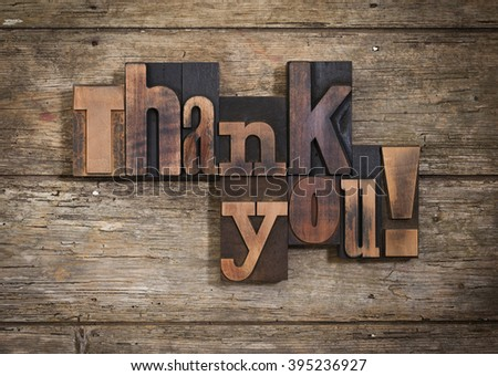 thank you, phrase set  on two lines with vintage letterpress printing blocks on rustic wooden background - stock photo