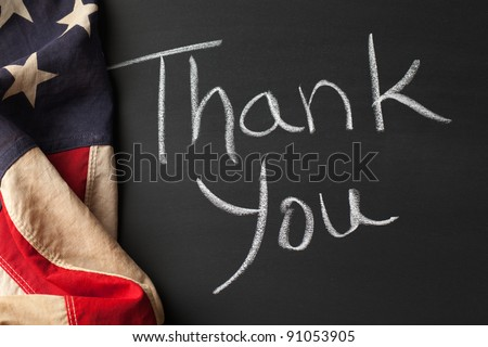 Thank you sign on a chalkboard with vintage American flag - stock photo
