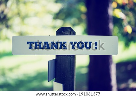 Thank you signboard on a wooden post in a faded retro image. - stock photo