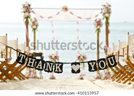 thank you words banner at beautiful beach wedding set up chairs flowers banana leaf cone - stock photo