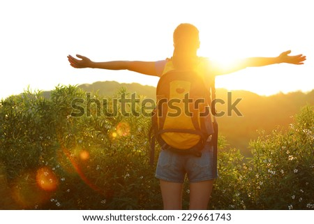 thankful woman hiker open arms to the sunrise stand at mountain peak  - stock photo