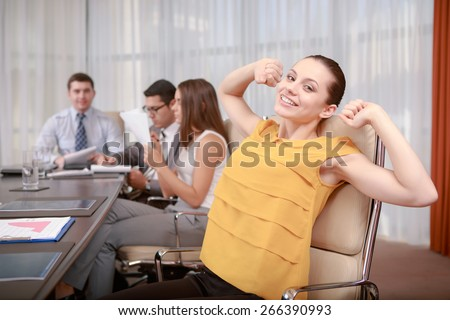 Thanks God it is Friday. Young smiling business manager stretching at a meeting while her partners sitting in a row around the table in blurry - stock photo