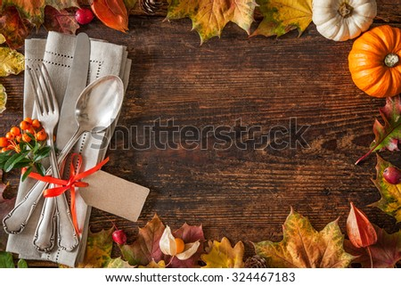 Thanksgiving autumn place setting with cutlery and arrangement of colorful fall leaves - stock photo