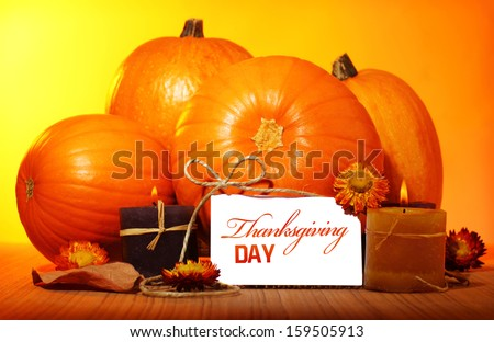 Thanksgiving day decoration for holiday celebration, pumpkin with greeting card on wooden table on yellow background, autumn season concept - stock photo