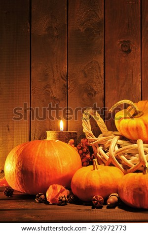 Thanksgiving - different pumpkins in rattan basket in front of old weathered wooden boards in candle light - stock photo