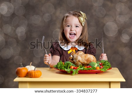 Thanksgiving Dinner.  Adorable little girl sitting at a small table with a small turkey (chicken) on a bed of greens and other vegetables.  Room for your text. - stock photo