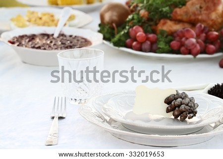 Thanksgiving Holiday table setting with cranberry sauce, deviled eggs and roast turkey in background. Blank note card placed on plate. Extreme shallow DOF with selective focus on center of plate. - stock photo