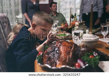 Thanksgiving: Hungry Boy Takes A Bit Of Turkey To Taste - stock photo