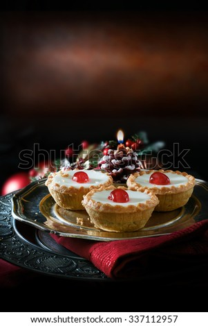 Thanksgiving or Christmas festive iced pastry mince pies on antique pewter plate against a rustic background with accommodation for copy space. - stock photo