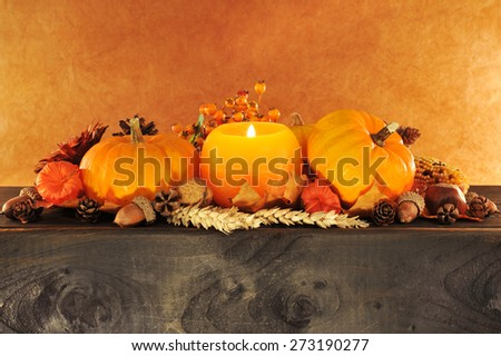 Thanksgiving - pumpkins in candle light on old weathered wooden boards in front of brown background - stock photo