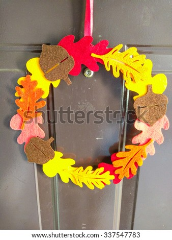 Thanksgiving wreath hanging on home entrance doors. - stock photo