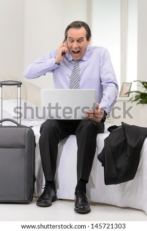 That is all wrong! Happy mature businessman sitting on the sofa at the hotel room with a laptop on his knees and shouting at the mobile phone - stock photo