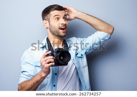 That is just amazing! Excited young man holding digital camera and looking way while standing against grey background - stock photo