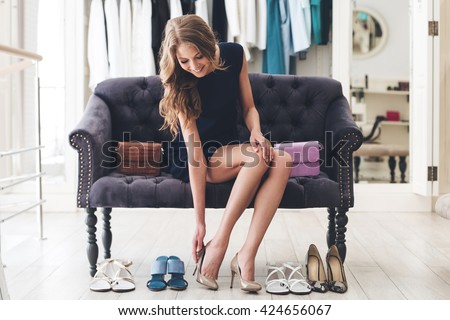 That is perfect pair! Beautiful young woman trying on high heel shoes while sitting on sofa at the shoe store - stock photo