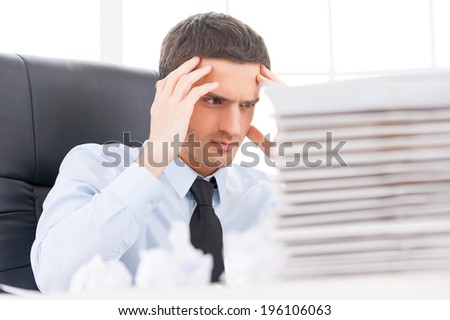 That is too much for me! Depressed young man in shirt and tie holding head in hands while sitting at the table with stack of paperwork on it - stock photo