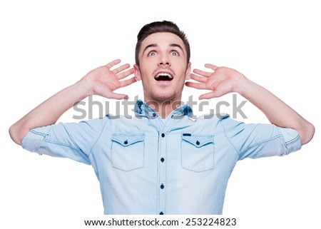 That is unbelievable! Surprised young man expressing positivity and gesturing while standing against white background - stock photo