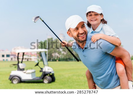 That was a good game. Cheerful young man piggybacking his son while standing on golf course - stock photo