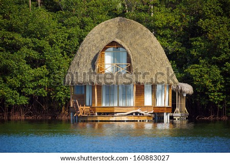 Thatched bungalow over water with lush tropical vegetation in background, Bocas del Toro, Caribbean sea, Central America, Panama - stock photo