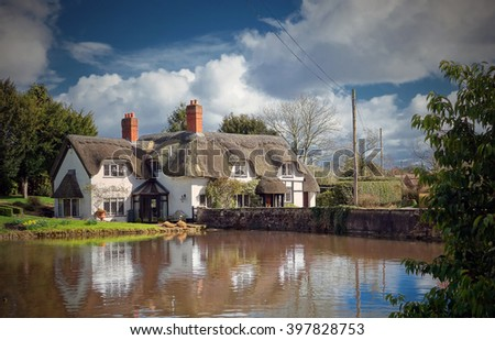 Thatched cottages behind duck pond in the idyllic English Village of Badger in Shropshire. - stock photo