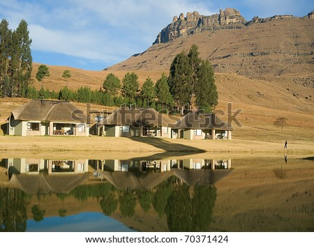 thatched holiday bungalow on a lake in the drakensberg mountains near underberg, kwazulu Natal, south africa. the drakensberg is a UNESCO world heritage site - stock photo