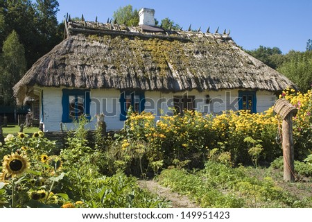Thatched roof house and a green garden in the countryside - stock photo