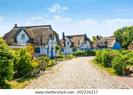 thatched-roof house settlement with cobbled stone street - stock photo