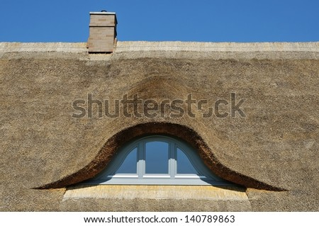 thatched roof with window and chimney - stock photo