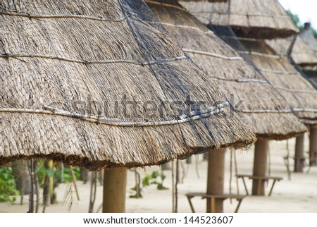 Thatched shelters on a tropical beach. - stock photo